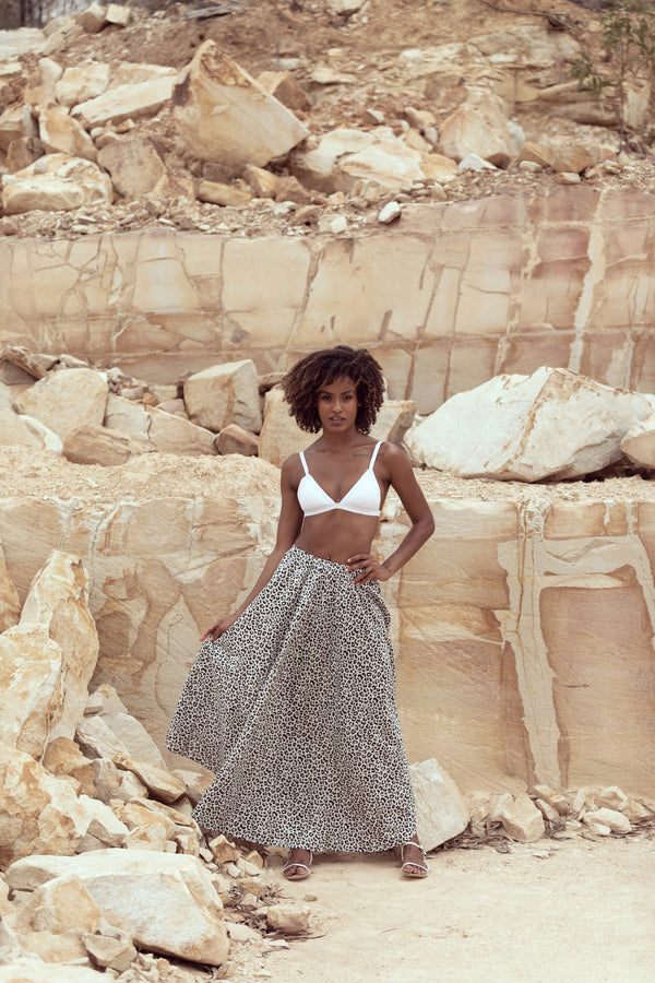 Model stands in sandstone quarry, modelling The Jane maxi skirt by Robe luxury resort wear in Snow Leopard print