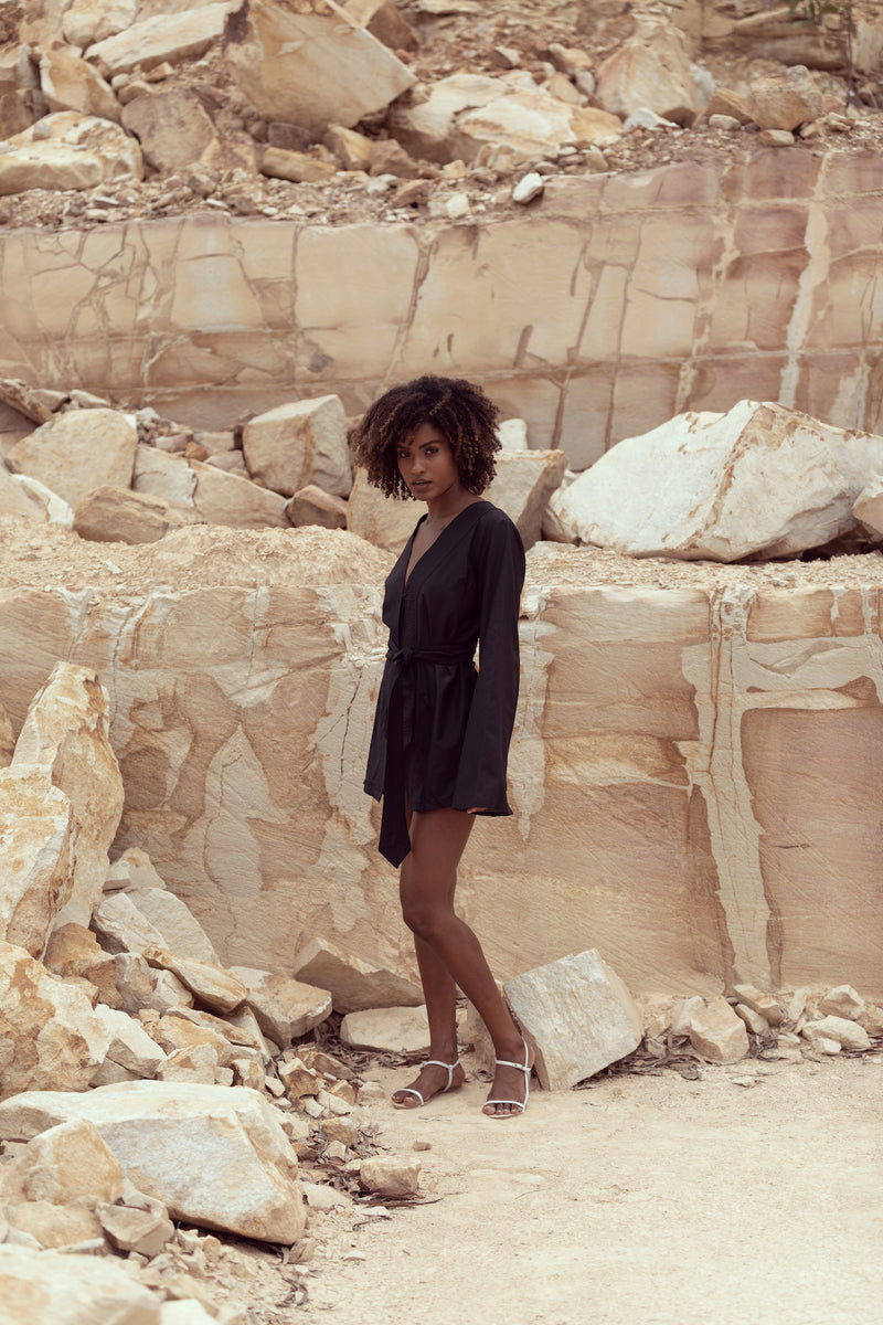 Woman stands in sandstone quarry, wearing The Isabelle tunic mini dress by Robe resort wear for women