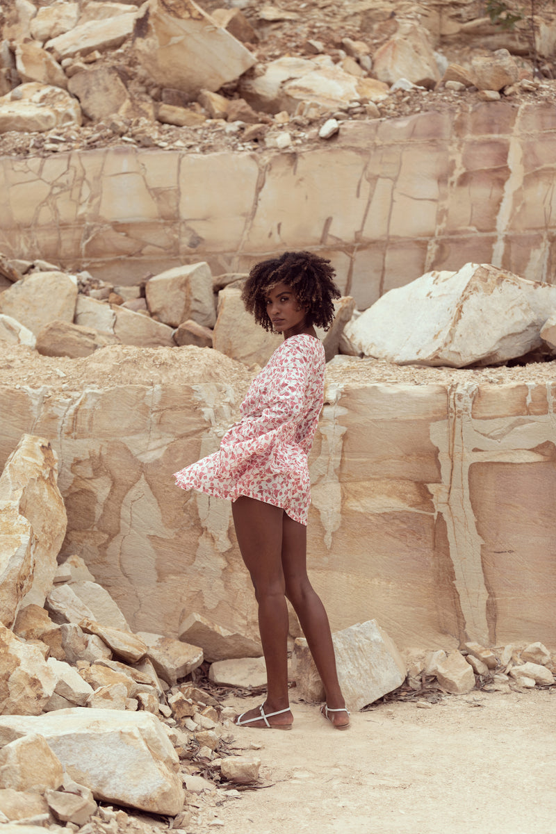 Model looks over shoulder, standing in Queensland sandstone quarry modelling The Isabelle in English Rose by Robe resort wear