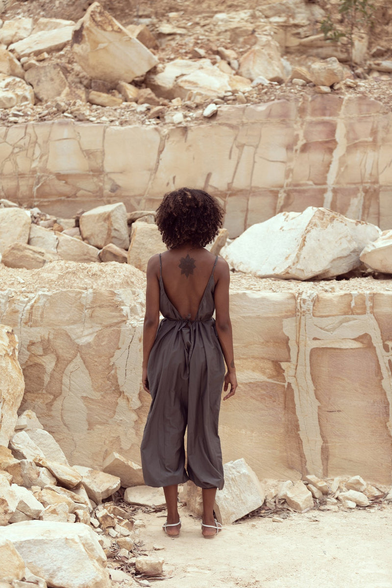 Woman shows the backless style of the Sarah J jumpsuit by Robe, standing in sandstone quarry