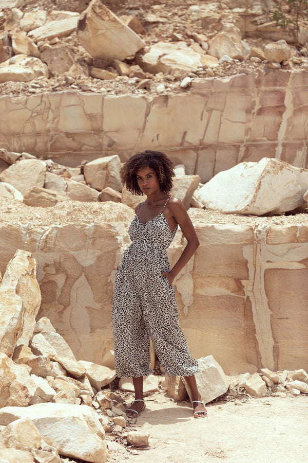 Woman poses in sandstone quarry, wearing silk jumpsuit The Sarah J in Snow Leopard by Australian designer Robe