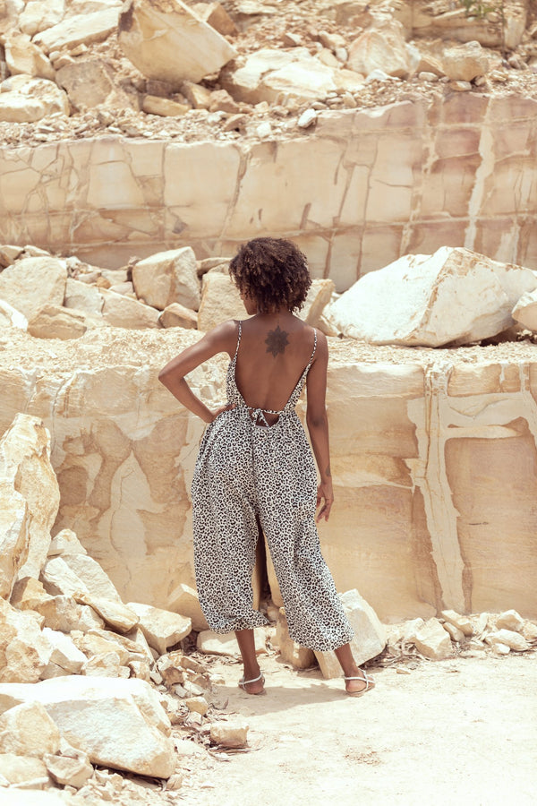 Woman shows backless leopard jumpsuit by Robe, a luxury resort designer