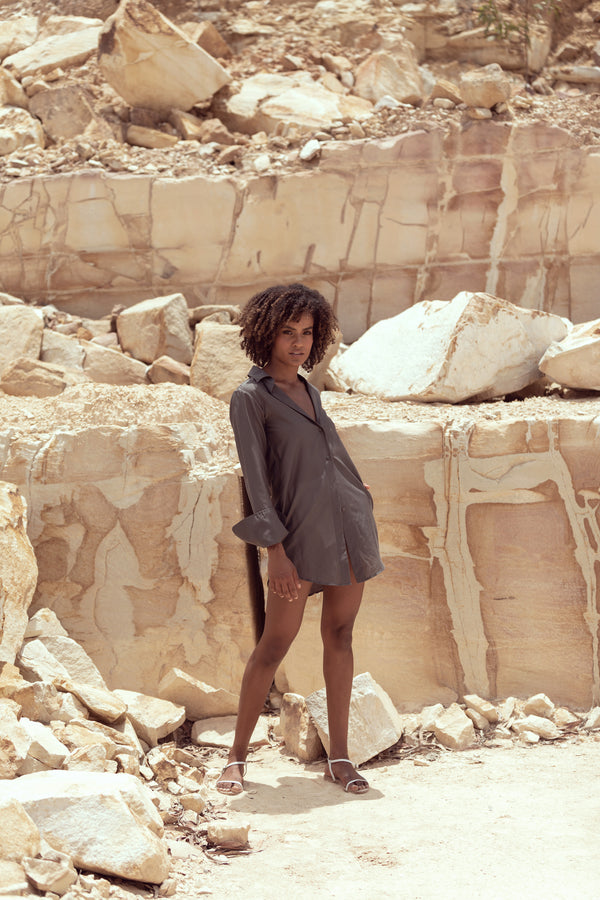 Model poses in canyon wearing charcoal grey button down silk shirt