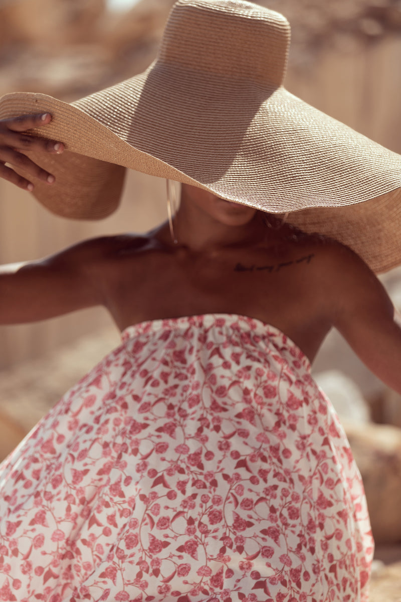 Woman looks down, wearing oversized straw hat and The Jane maxi skirt from Robe resort wear for women
