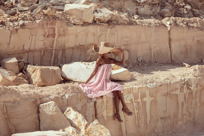 Model poses in editorial shot, sitting on cliff in sandstone quarry wearing The Jane maxi skirt by Robe resort wear with straw hat