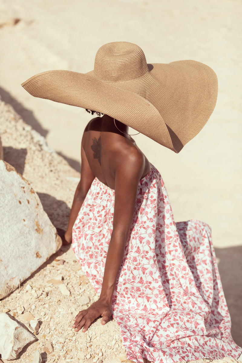Model sits on cliff, turned away from the camera wearing a straw hat and The Jane in english rose by Australian fashion label Robe