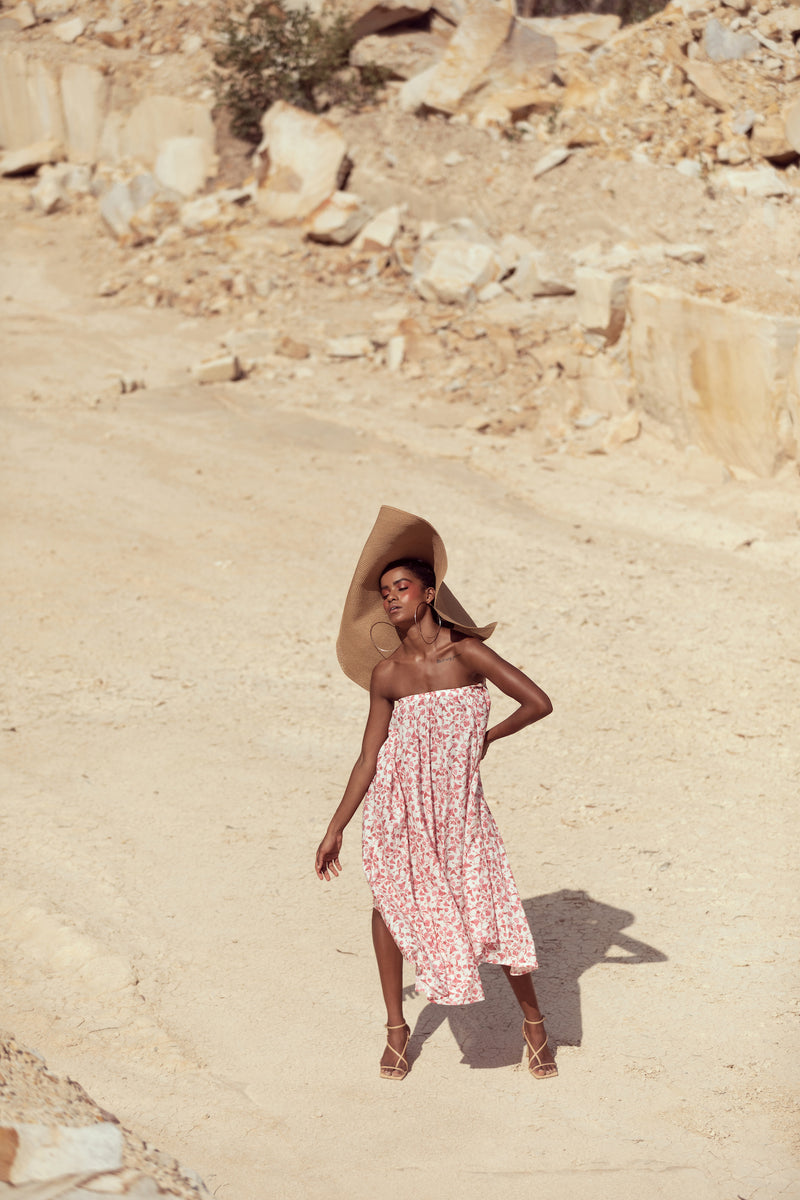 Model poses in editorial shoot, wearing large straw hat and The Jane by Australian fashion label Robe while in sandstone quarry