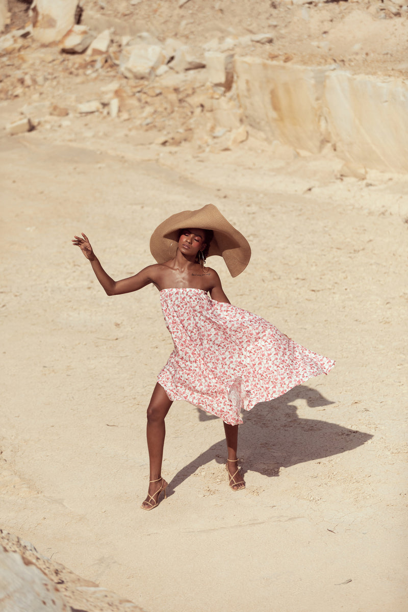 Model dances in sandstone quarry, wearing large straw hat and The Jane maxi skirt in English Rose by Robe resort wear for women