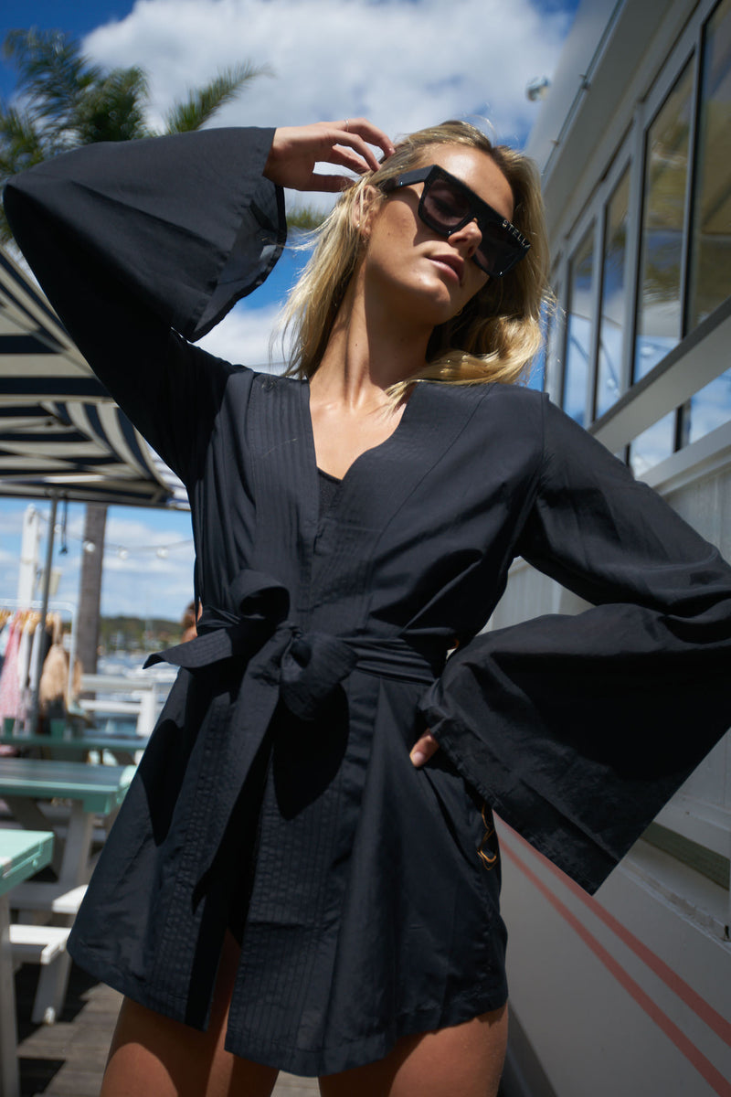 Blonde model poses at Watson's Bay Boutique Hotel, wearing The Isabelle by Australian fashion designer robe