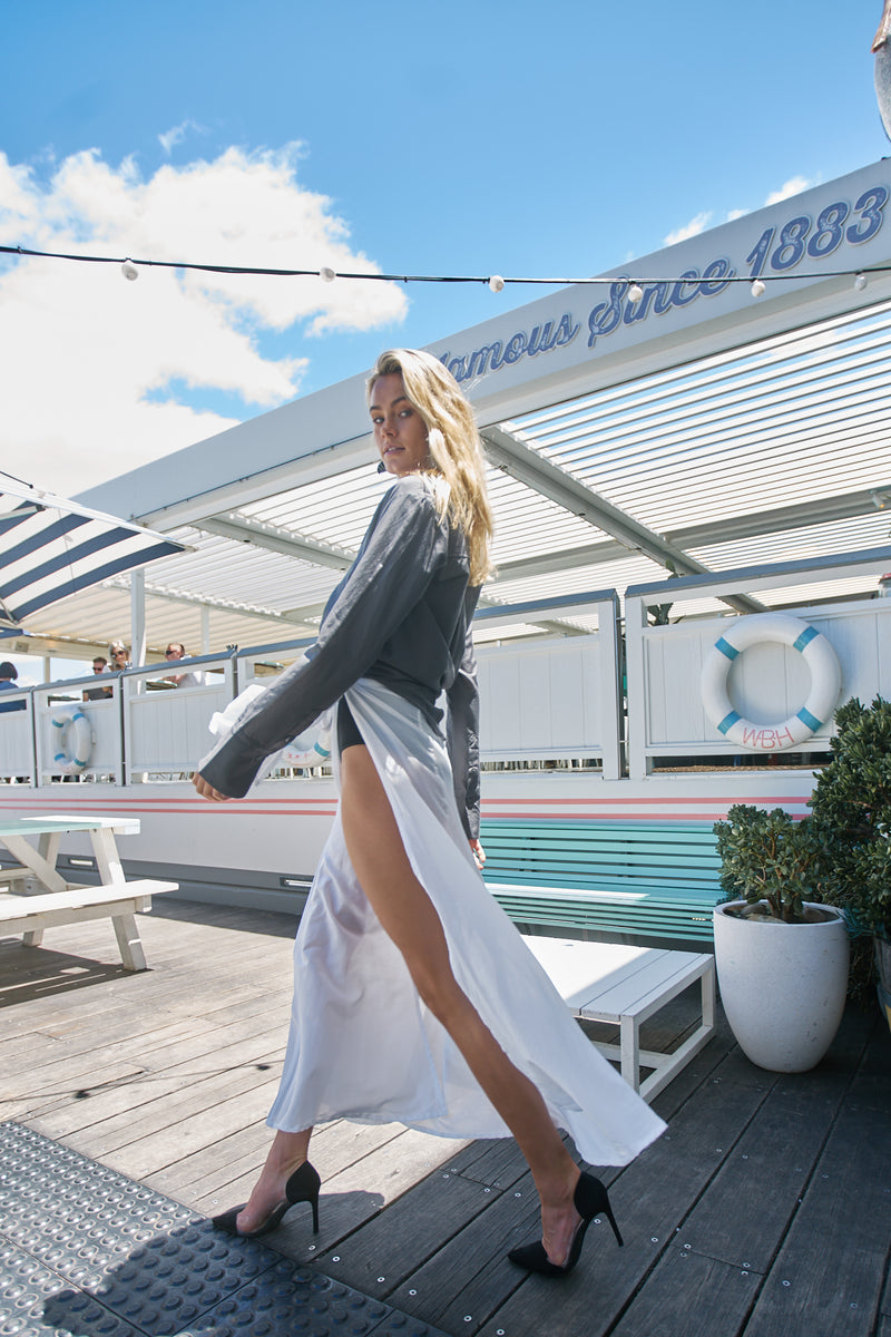 Model walks away on Watson's Bay Boutique Hotel deck, wearing The Bridget and The Molly by Robe resort wear for women