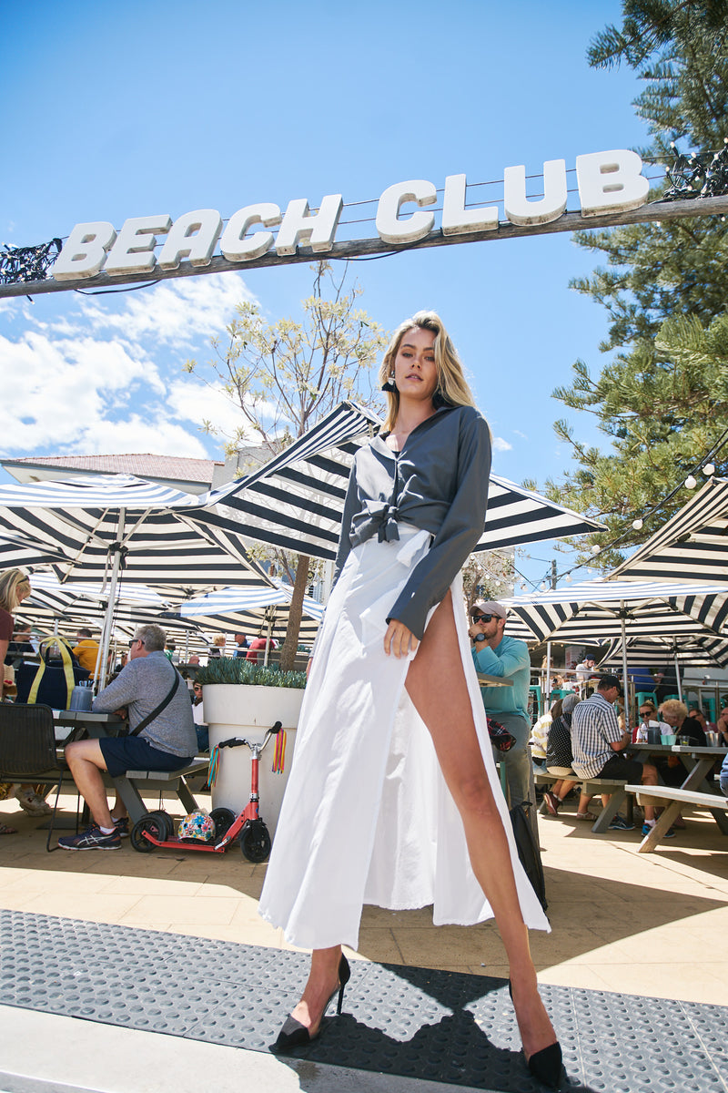 Model stands in front of striped umbrellas and diners, wearing a monochrome outfit by Robe luxury resort wear