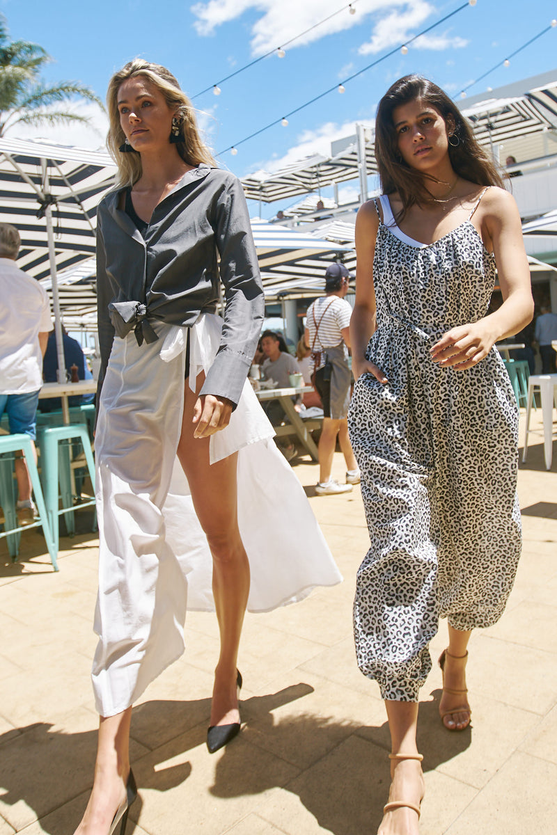 Two models walk among tables at Watson's Bay Boutique Hotel wearing outfits by Robe resort wear for women