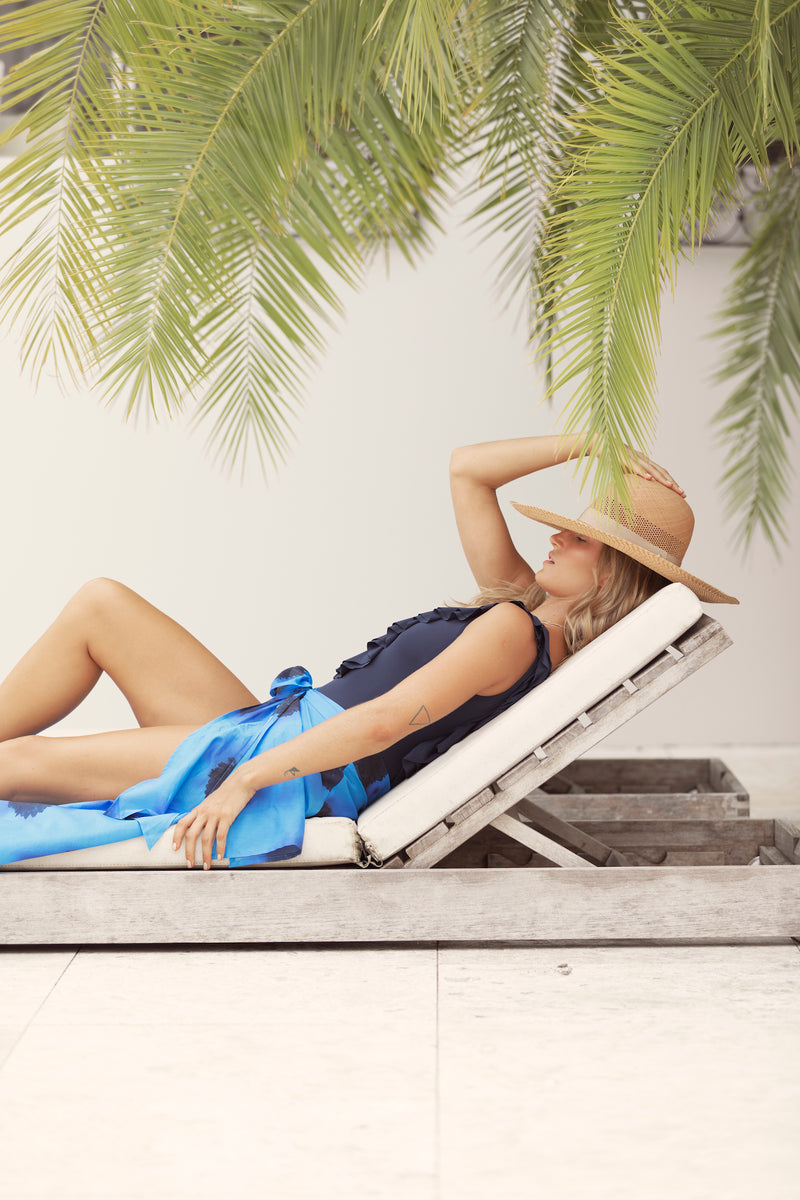 Blonde woman lies on pool lounge under palm tree, wearing a straw hat and The Molly in Black Chrysanthemum by Australian fashion label Robe