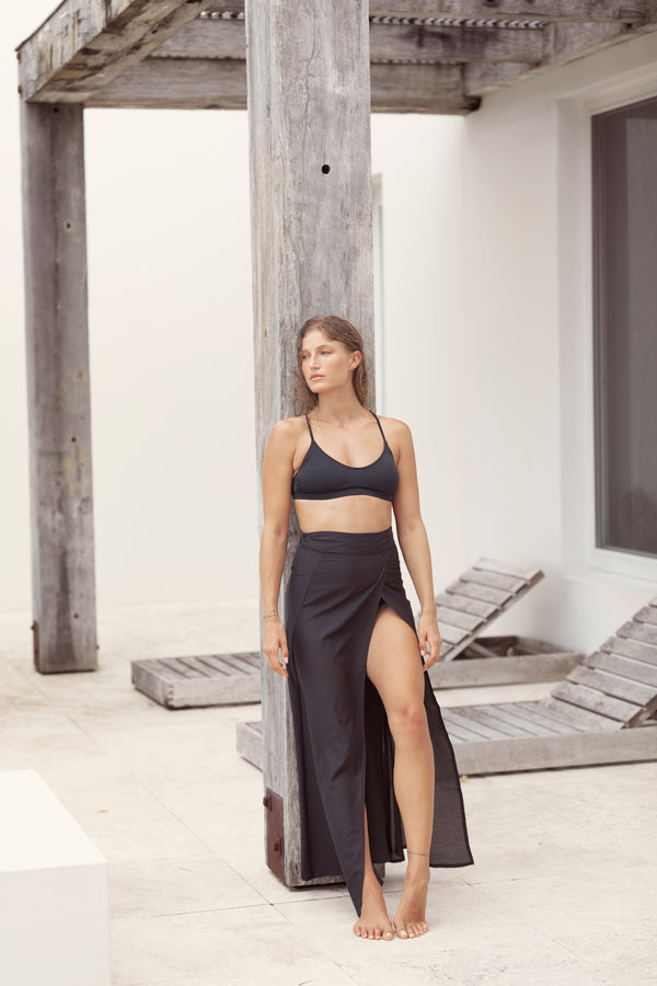 Blonde model leans on post at resort, staring into distance as she wears a black bikini and swim cover up The Molly maxi skirt from Australian fashion label Robe