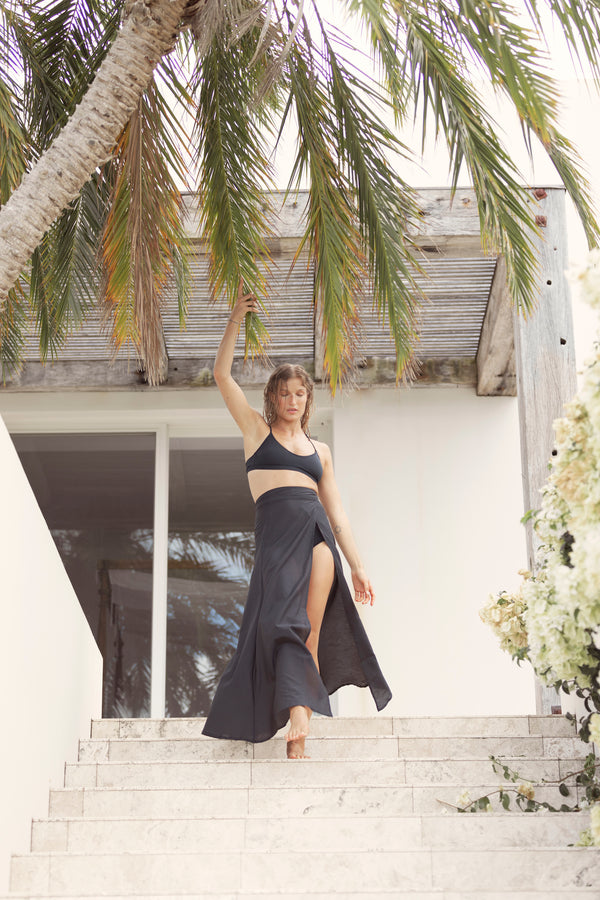 Model gets robed walking down the stairs, touching the palm tree above her as she wears The Molly maxi skirt in midnight from Robe luxury resort wear