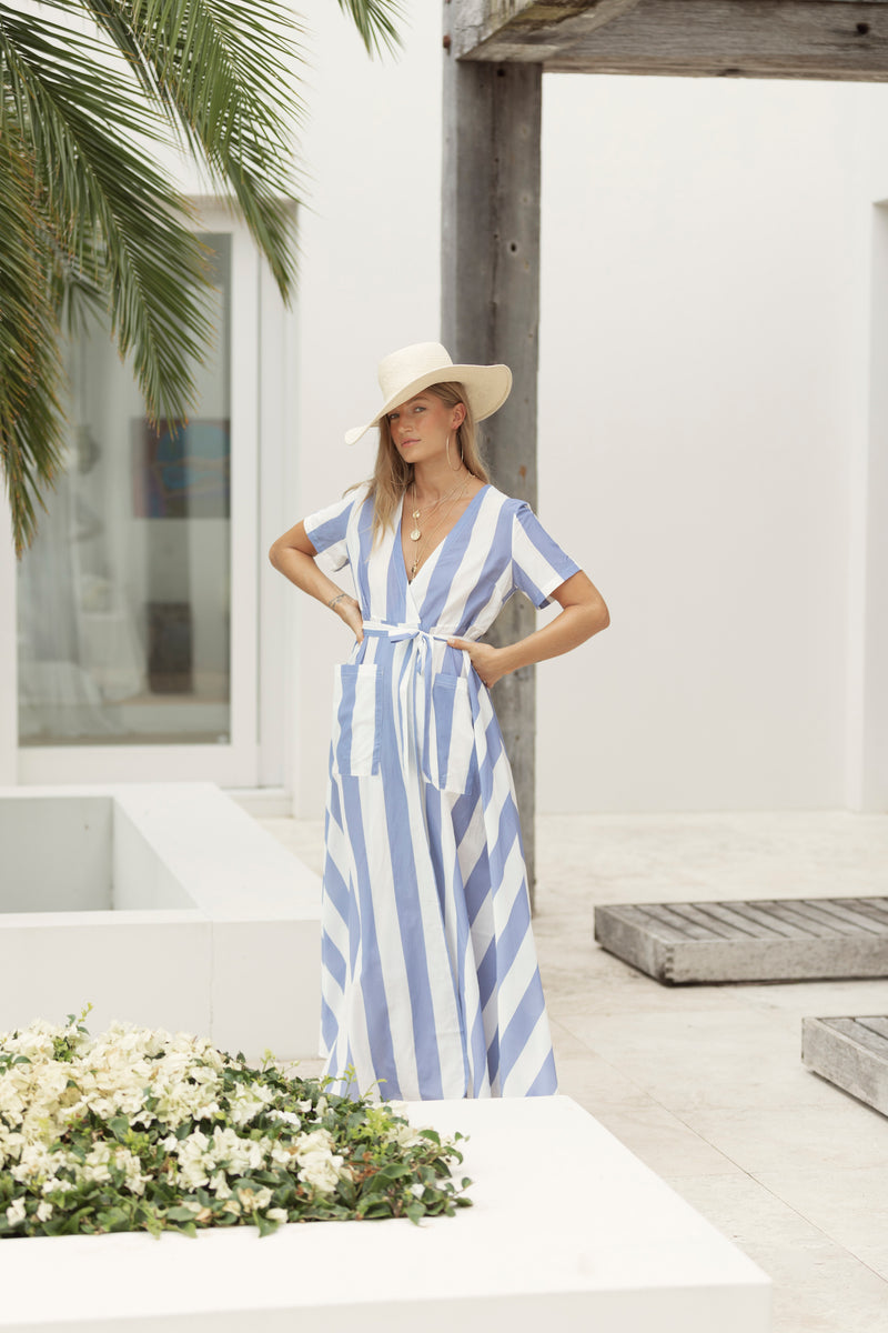 Blonde model stands at Byron Bay resort, wearing blue stripe maxi dress with white hat from Robe resort wear for women