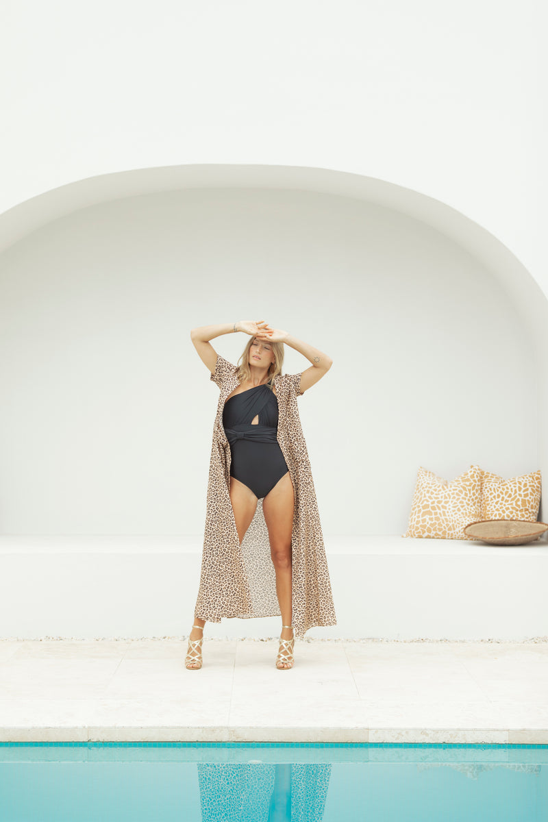 Model stands by pool, shielding face from sun as she models The Nikki maxi dress by Robe resort wear
