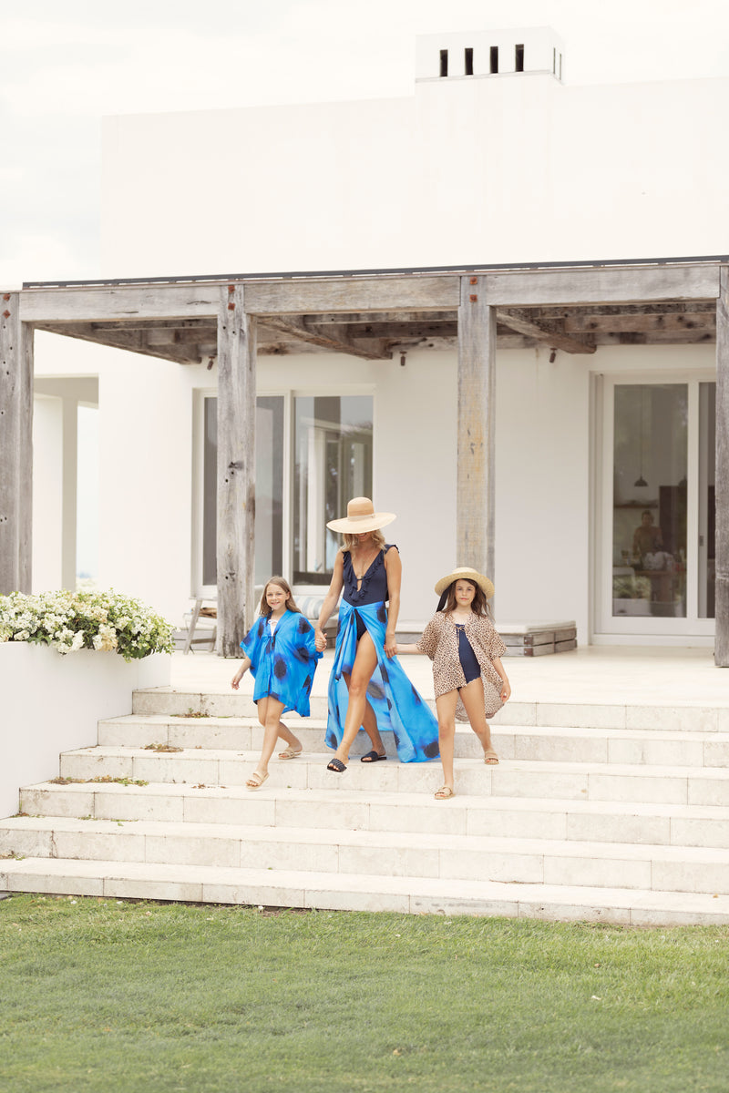 Woman and two girls stride down steps at Byron Bay resort, wearing Robe luxury resort wear