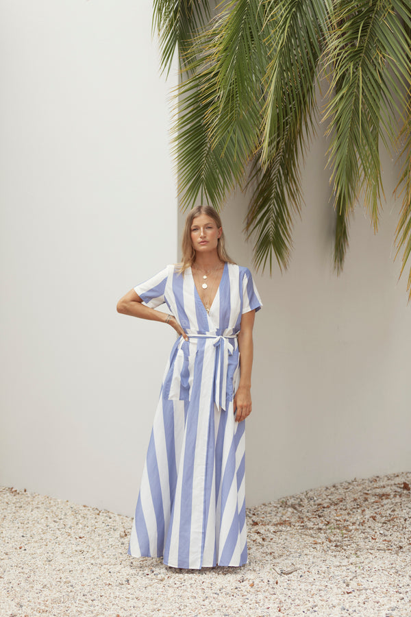 Model poses for ecommerce shot, wearing The Nikki silk maxi dress in blue stripe by Robe resort wear