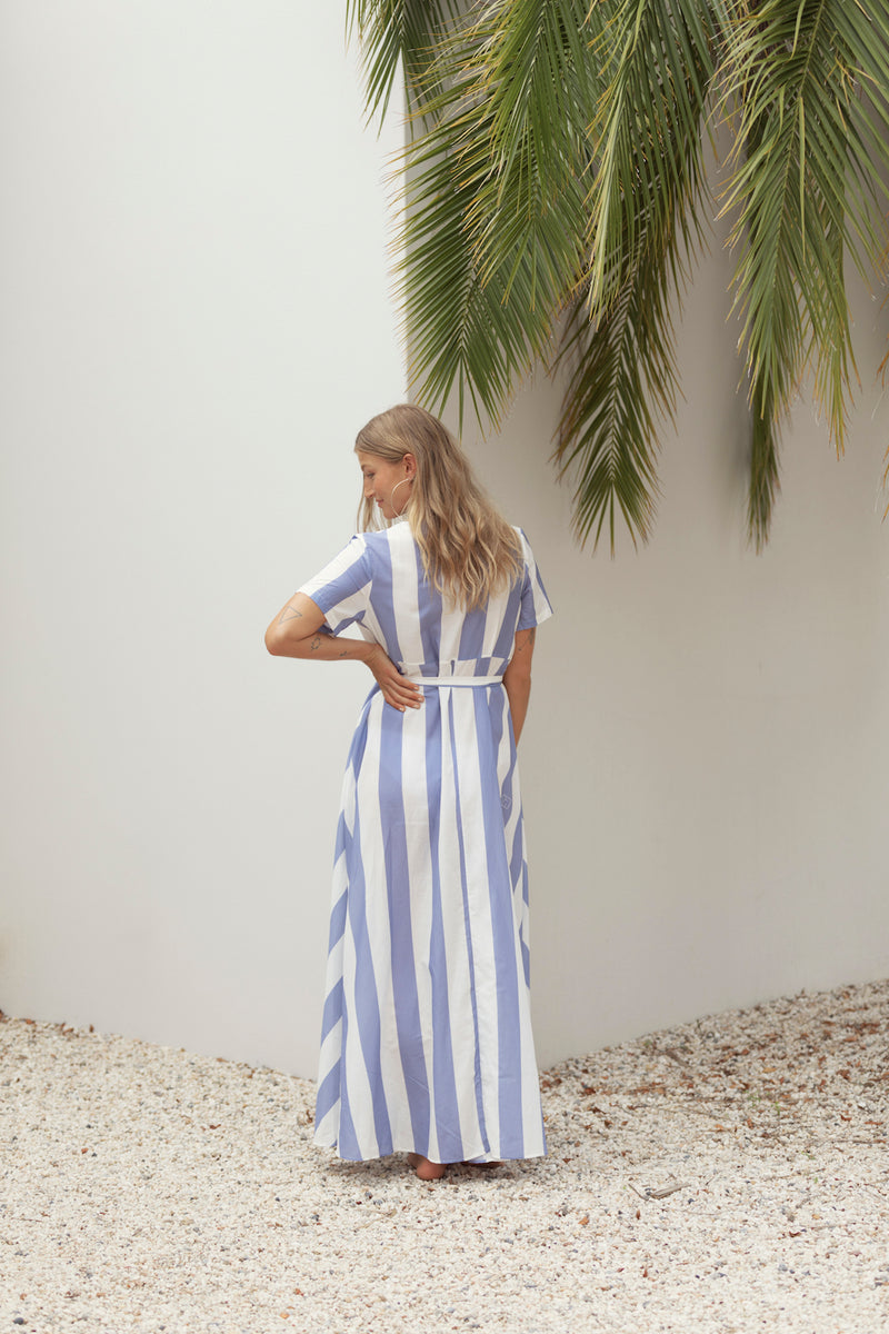 Model looks over shoulder as she poses in front of white all and palm fronds, wearing The Nikki maxi dress in Blue Streak from Australian resort label Robe