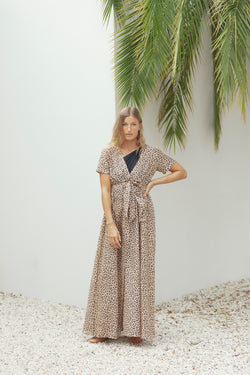 Woman poses in front of white wall, wearing The Nikki maxi dress in leopard from Australian fashion designer Robe