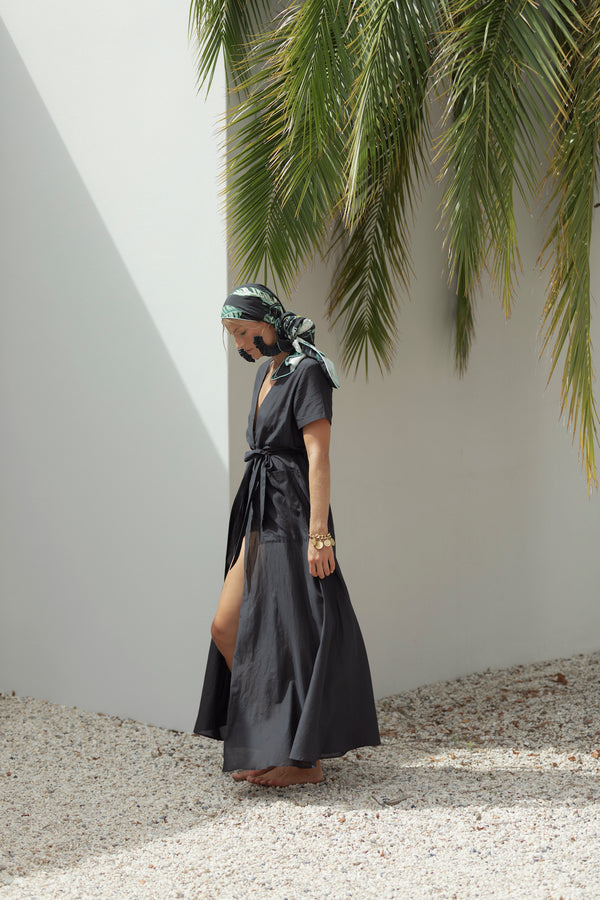Model turns to side, wearing The Nikki in Midnight by robe resort wear in front of white wall