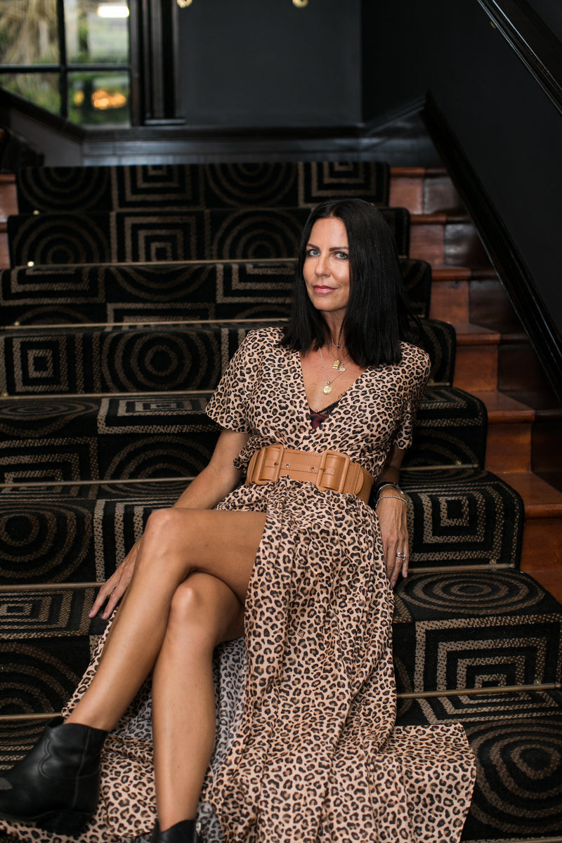 Woman lounges on carpeted stairs, wearing The Nikki in Leopard - a silk maxi dress by Robe resort wear