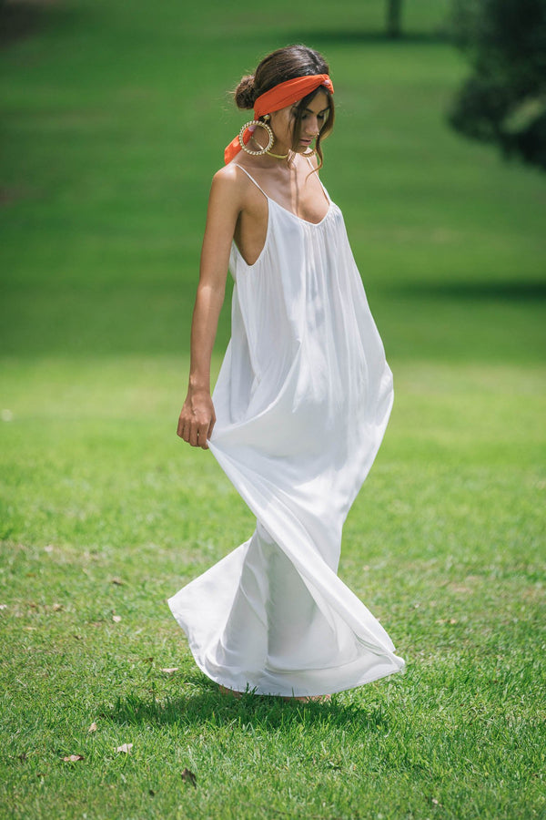 Model walks on grass wearing Robe resort wear Sarah maxi dress in Snow