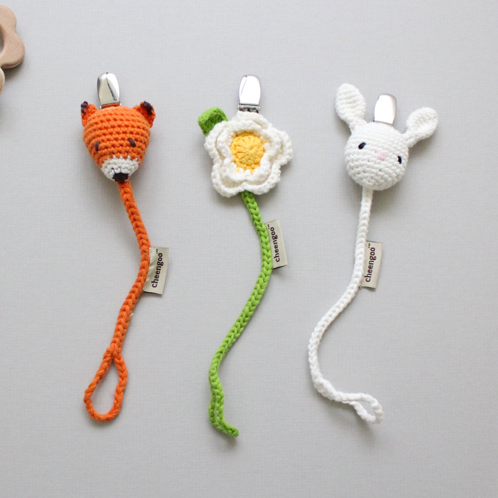 three cotton pacifier clips in fox, flower, and rabbit shapes