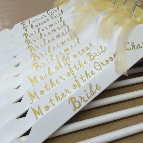 White hangers with gold writing and gold bow