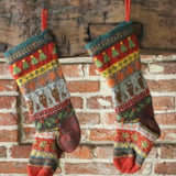 Knitted stocking in reds greens with reindeer and christmas trees on.