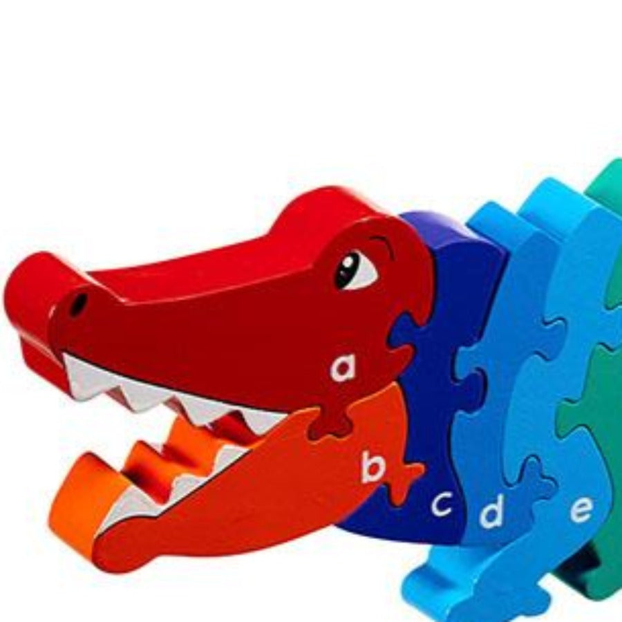 a crocodile shaped wooden jigsaw with the alphabet printed on.