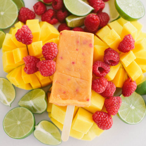 Orange popsicle sitting on top of mangos, raspberries, and limes.
