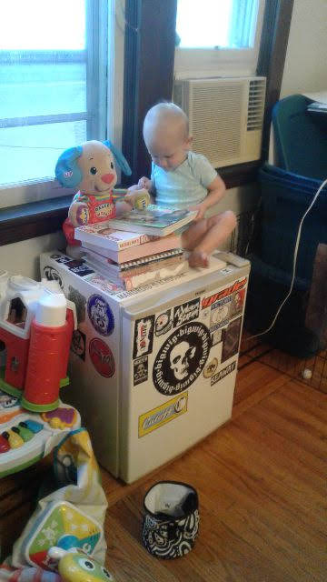 Small child sitting on a mini fridge reading a book