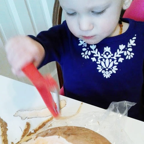 Child with a purple shirt sitting at the table with a plastic knife helping to prepare food