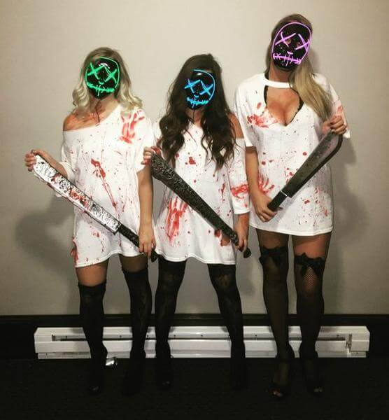 three girls wearing purge masks and costumes