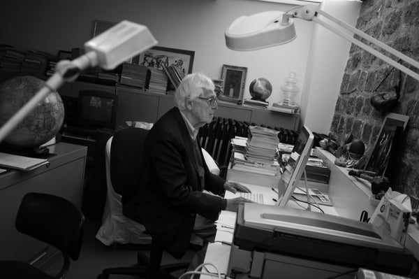 John Morris at his desk with photo of Robert Capa on his desk.