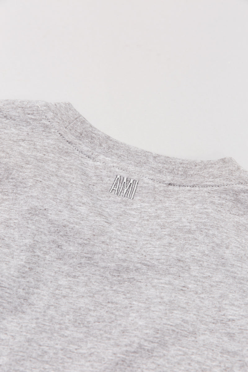 Back detail on AMI t-shirt in heather grey laying on grey backdrop