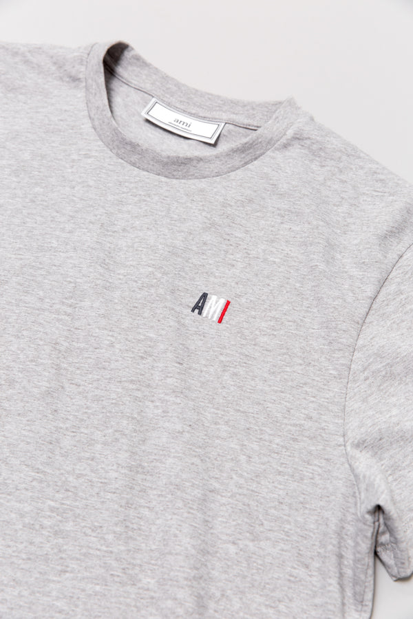Collar detail on AMI t-shirt in heather grey laying on grey backdrop