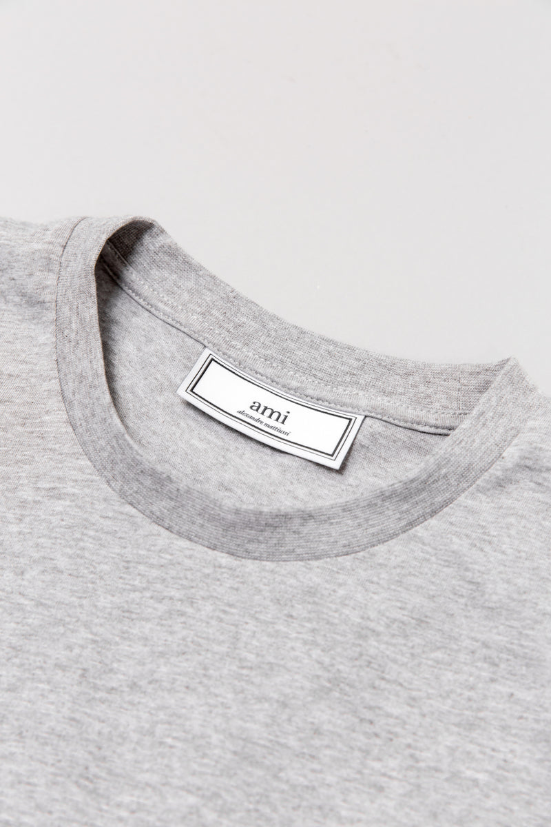 Tag detail on AMI t-shirt in heather grey laying on grey backdrop