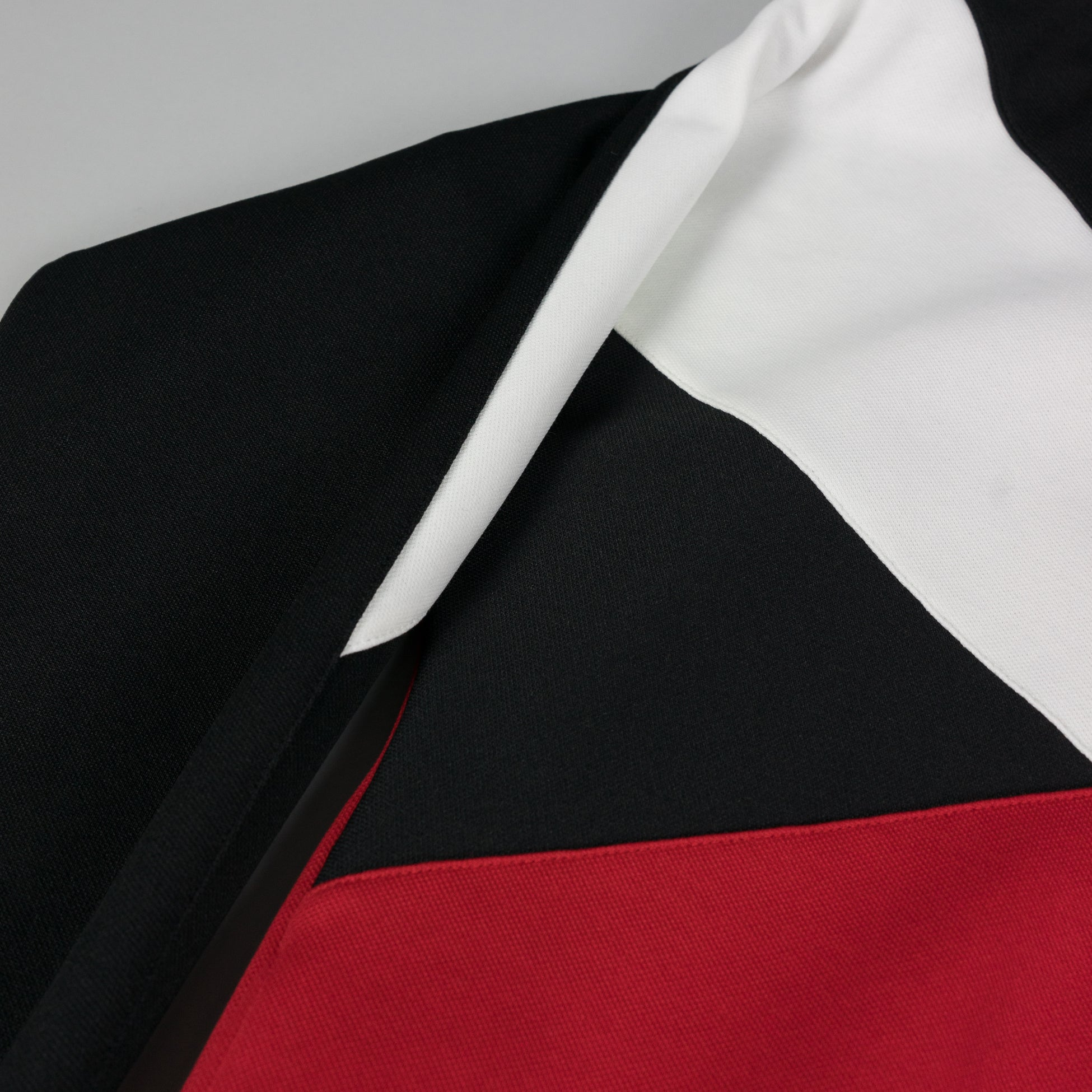 Close up detail of Maison Margiela Track Jacket in black, red, and white at ROOTED