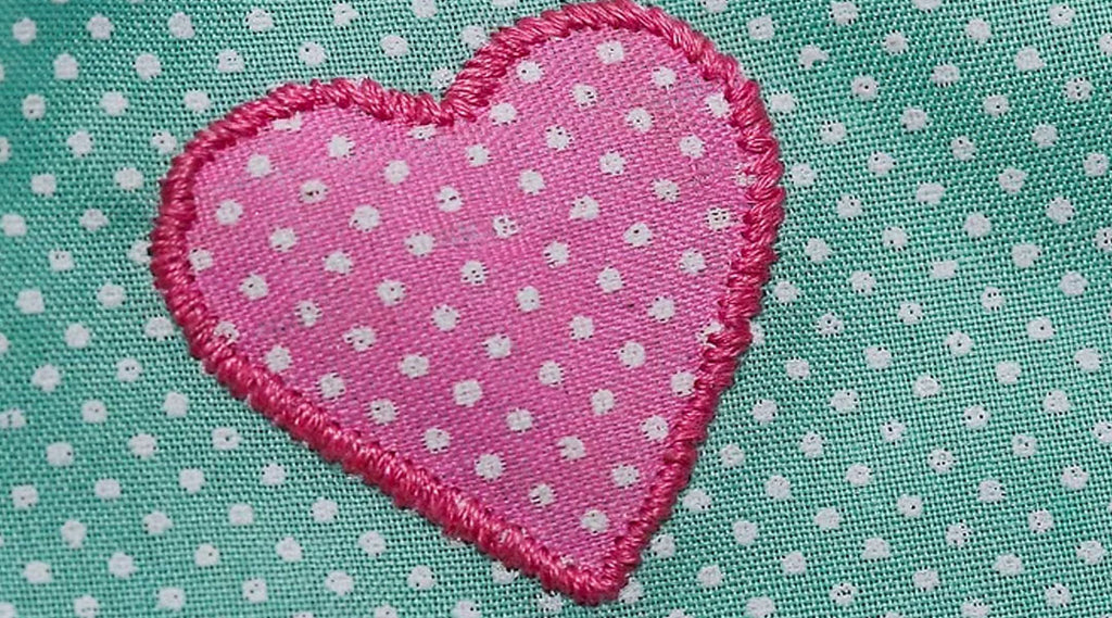This is an example of applique, notice how the heart is a different material and is attached to the base material using an outline stitch. Courtesy of WikiHow