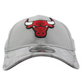 Embroidered on the front of the Chicago Bulls gray shadow camo brim dad hat is the Bulls logo embroidered in red, white, and black