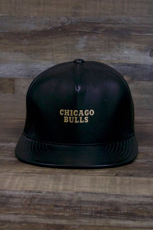 the front of the Chicago Bulls Leather Snapback | Black Bulls Snap Back with Gold Foil Design has chicago bulls written on it in gold
