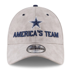 Embroidered on the front of the America's Team Dallas Cowboys Premium Gray Leather 2018 NFL Draft Dad Hat is the Dallas Cowboys logo embroidered in navy blue above the words America's Team embroidered in navy blue