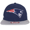 the new england patriots sideline snapback hat has a navy blue crown and a gray flat brim with the new england patriots logo embroidered in red, blue, and white on the front