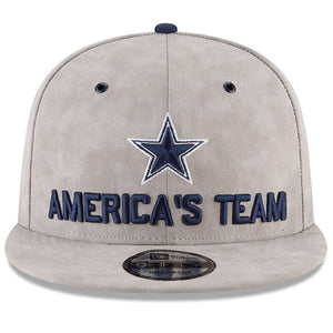 On the front of the gray leather Dallas Cowboys 2018 Draft Snapback Hat is the Dallas Cowboys logo embroidered in navy blue and white about the words America's Team embroidered in navy blue