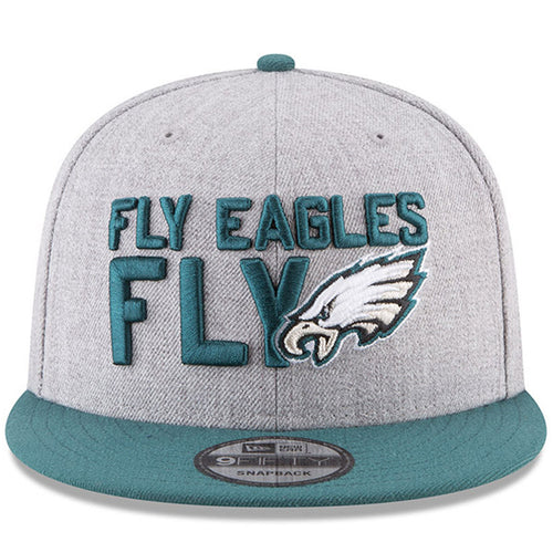 on the front of the Philadelphia Eagles on-stage 2018 NFL Draft snapback hat is the Fly Eagles Fly lettering embroidered in midnight green next to the Philadelphia Eagles logo