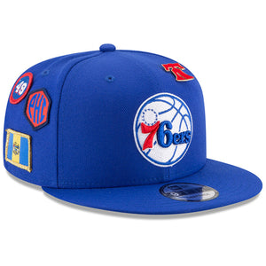 on the front of the 2018 Philadelphia 76ers Draft Snapback Hat is the Philadelphia 76ers logo embroidered in white, blue, and red