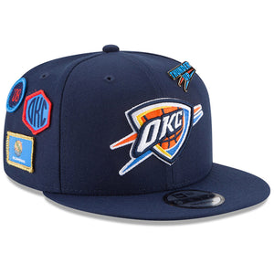 on the front of the oklahoma city thunder 2018 nba draft 9fifty snapback hat is the okc thunder logo embroidered in orange, black, yellow, white, and blue
